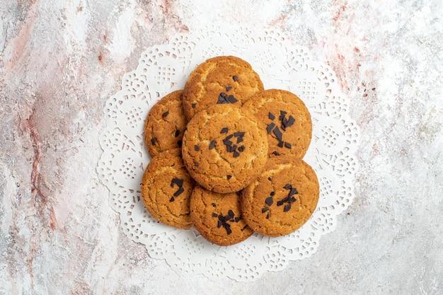Vista dall'alto di deliziosi biscotti di sabbia dolci perfetti per una tazza di tè sulla superficie bianca
