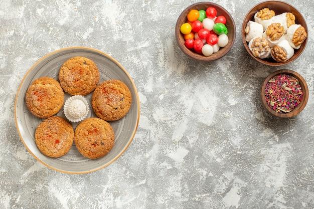 Vista dall'alto gustosi biscotti di sabbia con caramelle su sfondo bianco chiaro