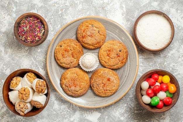 Вид сверху вкусное песочное печенье с конфетами на светло-белом фоне
