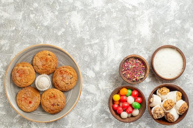 Vista dall'alto gustosi biscotti di sabbia con caramelle su sfondo bianco