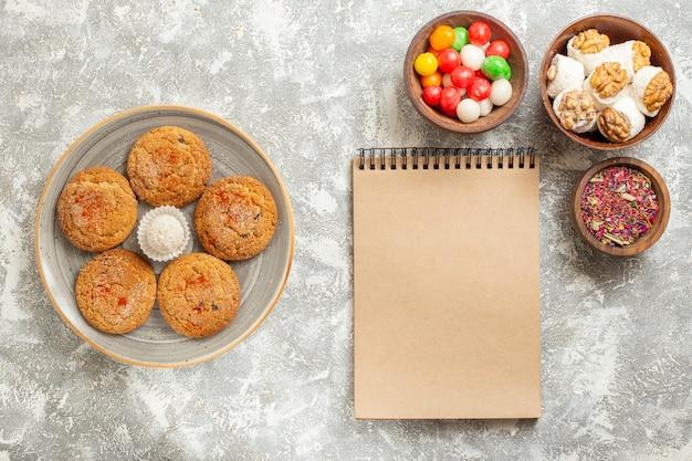 Vista dall'alto gustosi biscotti di sabbia con caramelle sul pavimento bianco