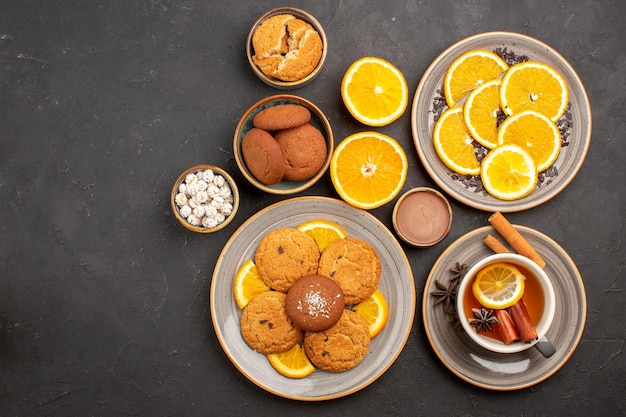 Top view yummy sand cookies with fresh oranges and cup of tea on dark background fruit biscuit sweet cookie citrus sugar