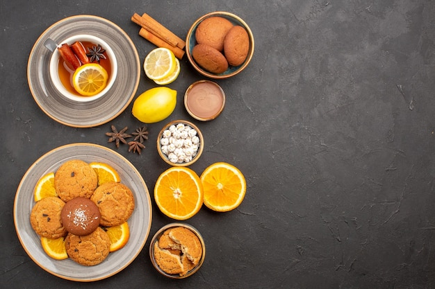 Top view yummy sand cookies with fresh oranges and cup of tea on dark background fruit biscuit sweet cookies citrus sugar