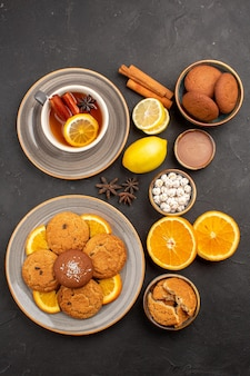 Top view yummy sand cookies with fresh oranges and cup of tea on dark background fruits biscuit sweet cookies citrus sugar