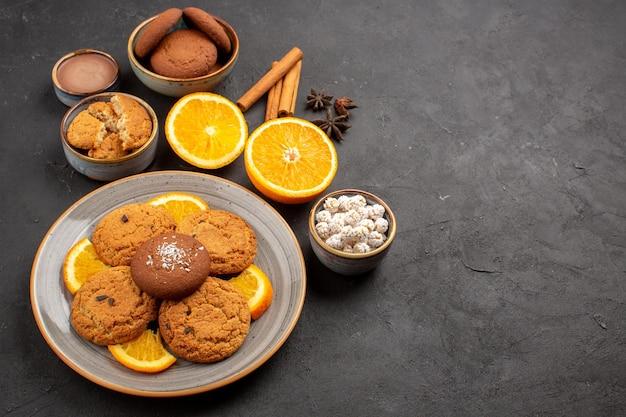 Vista dall'alto deliziosi biscotti di sabbia con arance fresche a fette su sfondo scuro biscotto alla frutta biscotto dolce zucchero agli agrumi