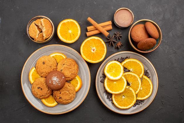 Vista dall'alto gustosi biscotti di sabbia con arance fresche a fette su sfondo scuro biscotto alla frutta biscotto dolce zucchero colore agrumato