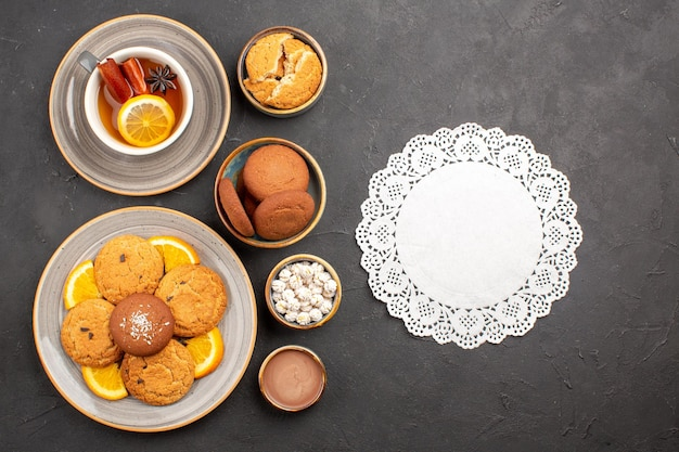 Top view yummy sand cookies with oranges and cup of tea on dark background biscuit fruit citrus sweet cake cookie