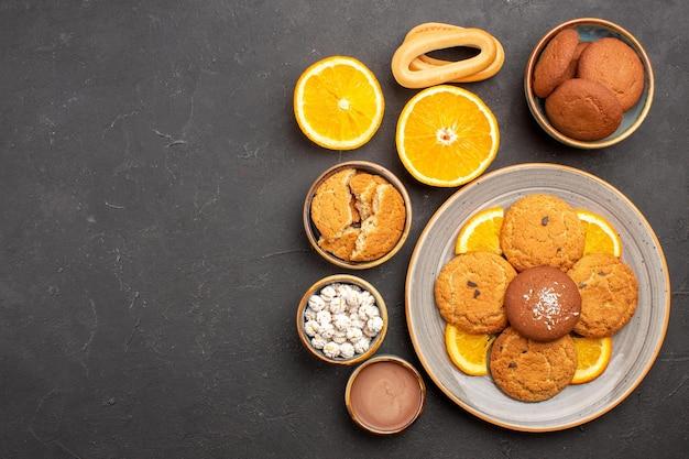 暗い背景にスライスしたオレンジとおいしい砂のクッキーの上面図フルーツ柑橘類のビスケットの甘いケーキクッキー