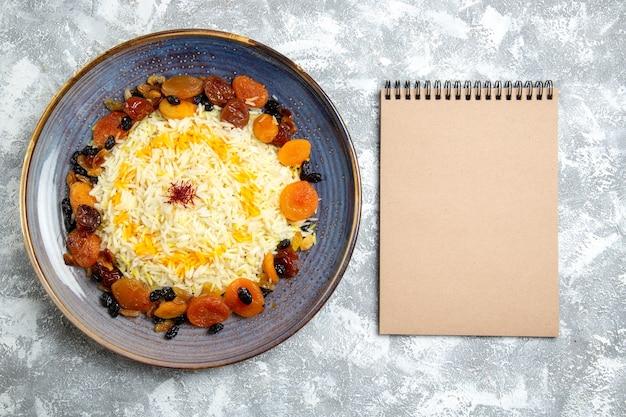 Vista dall'alto yummy shakh plov cotto piatto di riso con uvetta all'interno della piastra su bianco chiaro