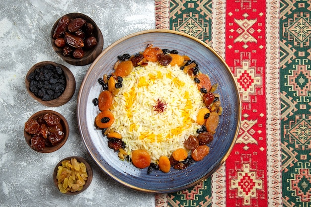 Top view yummy shakh plov cooked rice dish with raisins inside plate on light white