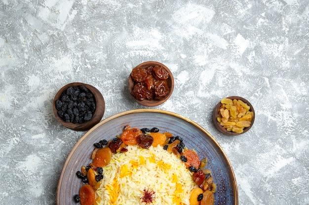 Вид сверху вкусный шах-плов, приготовленное блюдо из риса с изюмом внутри тарелки на белом