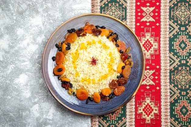 Вид сверху вкусный шах-плов, приготовленное блюдо из риса с изюмом внутри тарелки на белом столе