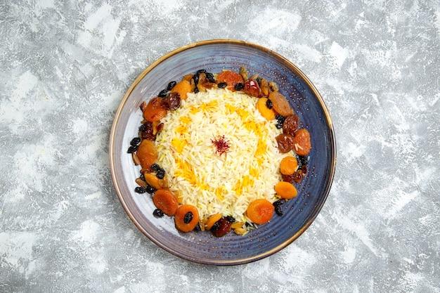 Vista dall'alto yummy shakh plov cotto piatto di riso con uvetta all'interno della piastra su bianco