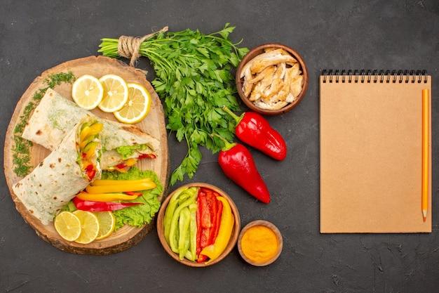 Vista dall'alto del delizioso sandwich di pollo a fette di shaurma con fette di limone e verdure al buio