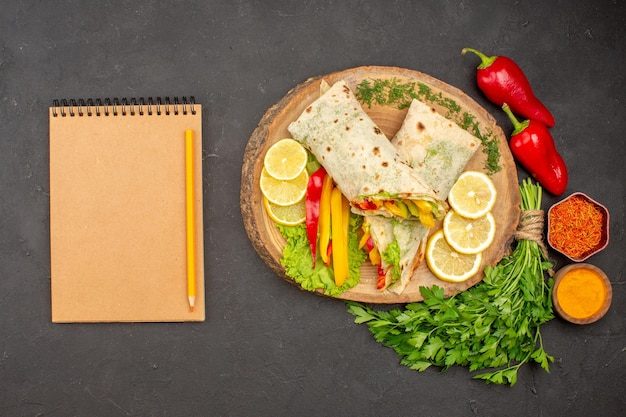 Vista dall'alto del delizioso sandwich di pollo a fette di shaurma con verdure al limone al buio