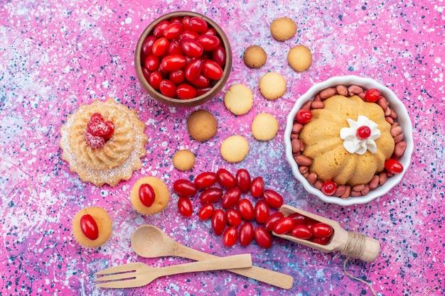 Вид сверху вкусный простой торт со сливками и свежим арахисом печенье из красного кизила на ярком свете настольный торт бисквитный сладкий орех ягода