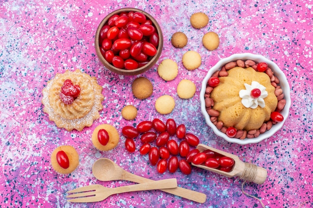 Top view yummy simple cake with cream and fresh peanuts red dogwoods cookies on the bright light desk cake biscuit sweet nut berry
