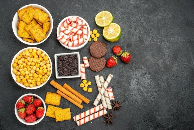 Вид сверху вкусные закуски с крекерами, кусочками шоколадных ломтиков лимона на черном фоне со свободным пространством