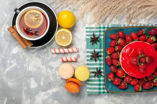 Вид сверху вкусный клубничный торт со свежей клубникой, чашкой чая и макаронами на белом столе