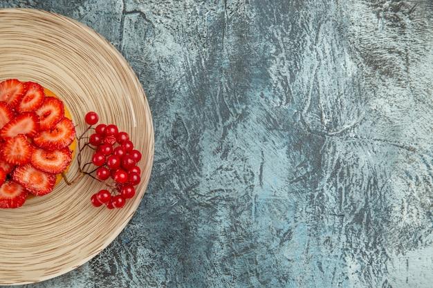暗い机の上に赤いベリーとおいしいストロベリーケーキの上面図