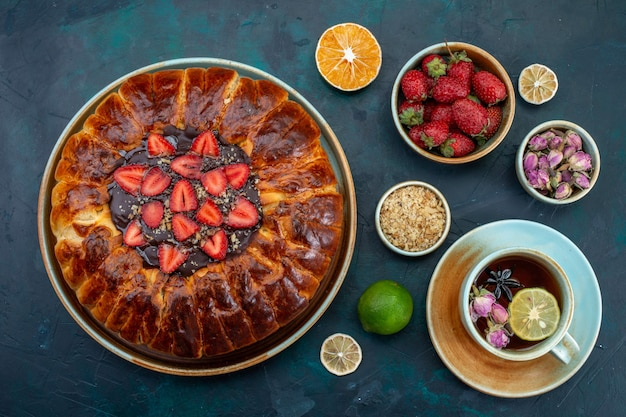 Top view of yummy strawberry pie baked delicious cake with cup of tea on dark-blue surface