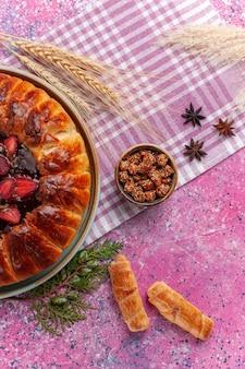 Vista dall'alto torta fruttata gustosa torta di fragole con bagel sul rosa