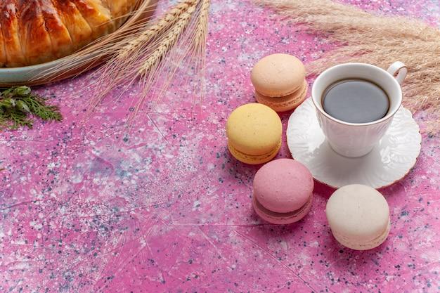 Вид сверху вкусный клубничный пирог с чашкой чая и макаронами на розовом