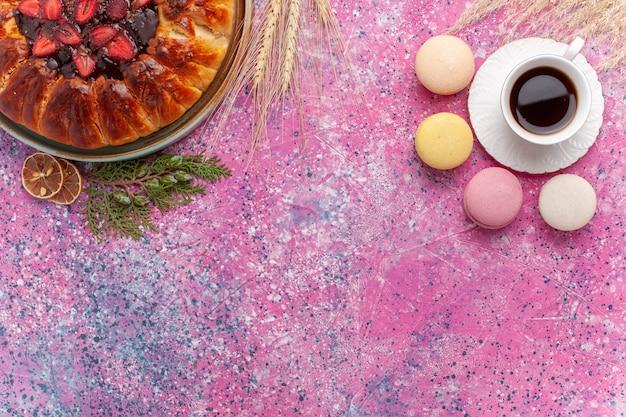 Torta di fragole squisita vista dall'alto con una tazza di tè e macarons sul rosa