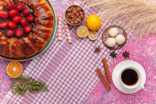 Torta di fragole gustosa vista dall'alto con una tazza di tè sul rosa