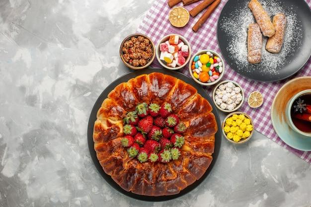 Vista dall'alto di gustosissima torta di fragole con caramelle di fragole rosse fresche e tazza di tè sulla superficie bianca
