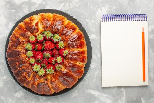 Vista dall'alto di una deliziosa torta di fragole con fragole rosse fresche e blocco note sulla superficie bianca