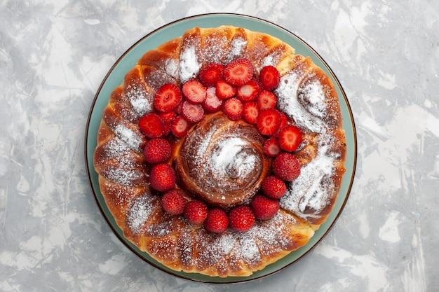 Вид сверху вкусный клубничный пирог с сахарной пудрой на белом фоне
