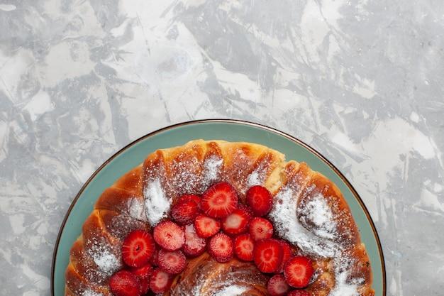 Вид сверху вкусный клубничный пирог с сахарной пудрой на белом столе