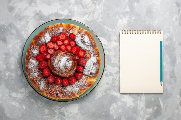 Torta di fragole gustosa vista dall'alto con zucchero in polvere su sfondo bianco