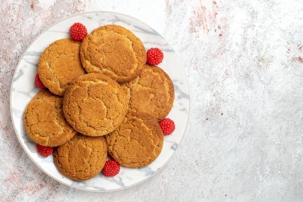 Vista dall'alto di deliziosi biscotti di zucchero all'interno della piastra sulla superficie bianca