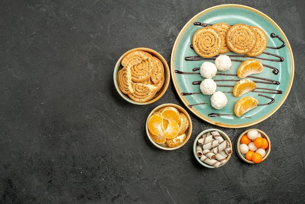 Vista dall'alto gustosi biscotti di zucchero con caramelle su sfondo grigio scuro