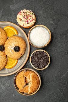 Top view yummy sugar cookies with orange slices on dark surface cookie biscuit sweet tea cake