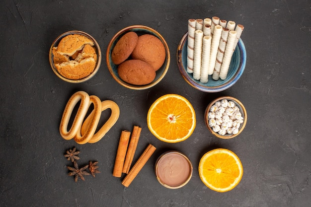 暗い背景にスライスしたオレンジとおいしいシュガークッキーの上面図シュガーティービスケットクッキー甘いフルーツ