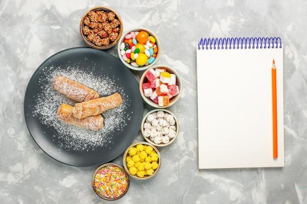 Vista dall'alto di deliziosi bagel dolci di zucchero a velo con diverse caramelle sulla superficie bianca