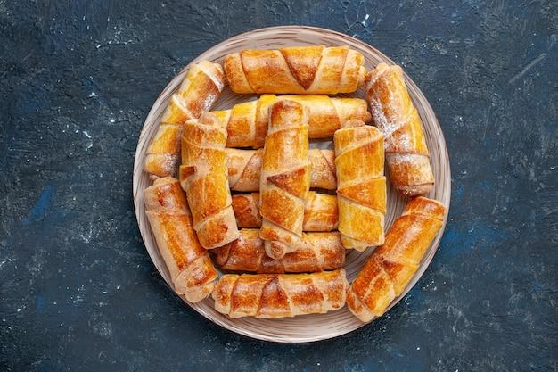 Vista dall'alto gustosi braccialetti dolci con ripieno all'interno del piatto sulla scrivania scura torta di biscotti dolci cuocere la pasticceria