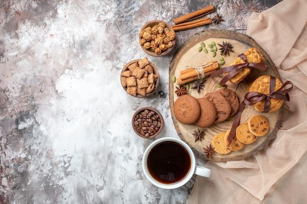 Vista dall'alto deliziosi biscotti dolci con una tazza di caffè sul tavolo luminoso