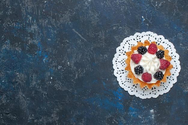Вид сверху вкусный сладкий торт с разными ягодами и кремом на темно-сером столе фруктово-ягодный цвет торт бисквитный сладкий