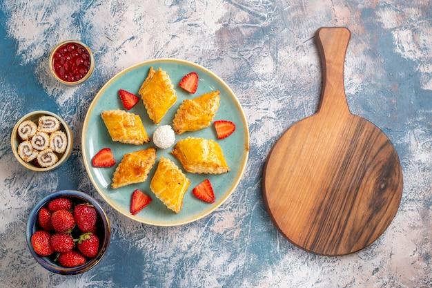 Вид сверху вкусные сладкие пирожные с фруктами на синем фоне