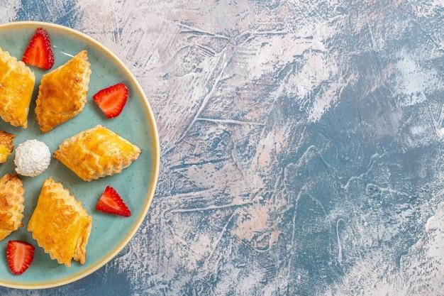 Вид сверху вкусные сладкие пирожные с клубникой на синем фоне