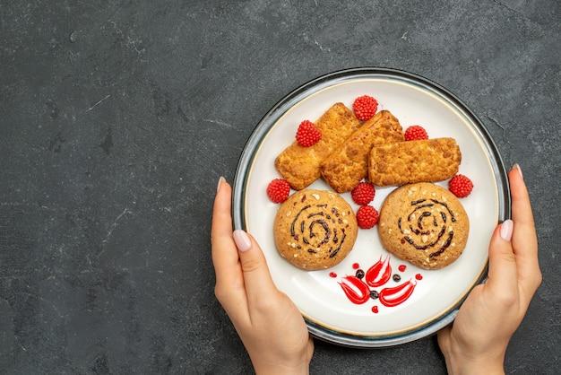 Вид сверху вкусное сладкое печенье внутри тарелки на сером фоне печенье сладкий сахарный торт печенье чай