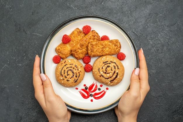 灰色の背景にプレート内のおいしい甘いクッキーの上面図ビスケット甘い砂糖ケーキクッキーティー