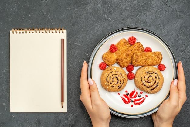 灰色の机の上のプレートの内側のおいしい甘いクッキーの上面図ビスケット甘い砂糖ケーキクッキーティー