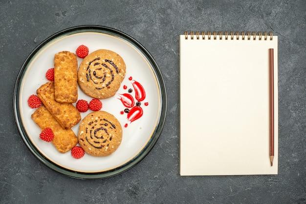 灰色の背景においしい甘いクッキーの上面図ビスケット甘い砂糖ケーキクッキーティー