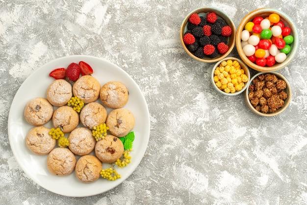 上面図白い背景の上のキャンディーとコンフィチュールとおいしい甘いクッキーシュガーケーキクッキーキャンディー