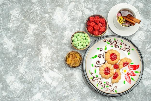 Vista dall'alto gustosi biscotti dolci con caramelle e tazza di tè su bianco